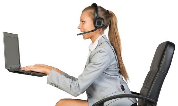 Businesswoman in headset, typing on laptop keyboard