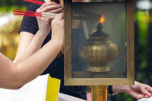 people lighting Incense sticks with lamp in Thailand