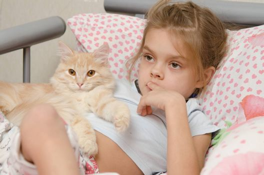 Six year old girl lying in bed with a young cat