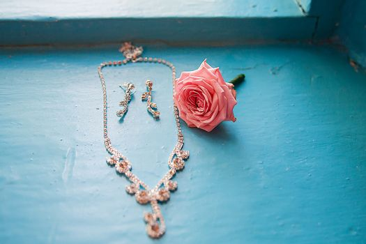 elegant rose with necklace and earrings on a blue