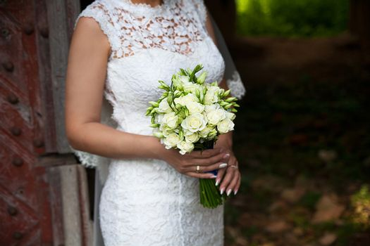 Bride holding wedding flower bouquet of roses.