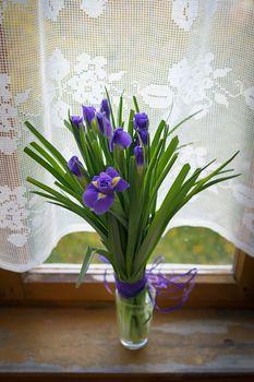 Purple iris flowers in vase, on wooden table