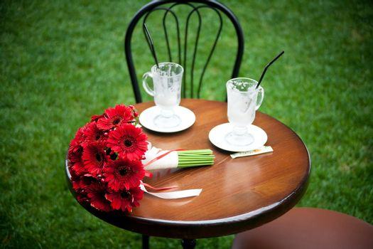 red bridal bouquet and cappuccino, coffee cup