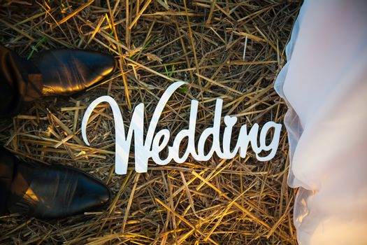 Feet of groom and bride. White wedding letters
