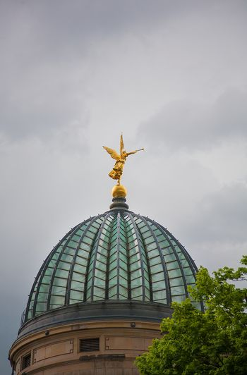 Golden angel statue with trumpet on the top