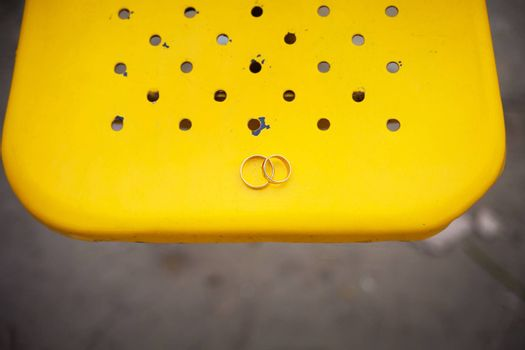 Two wedding rings on a yellow background.
