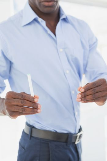 Businessman deciding between electronic or normal cigarette
