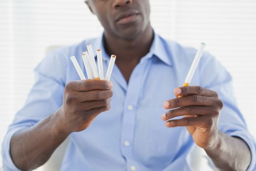 Businessman deciding between electronic or normal cigarettes