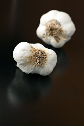 Garlic bulbs isolated over a black background.  Shallow depth of field.