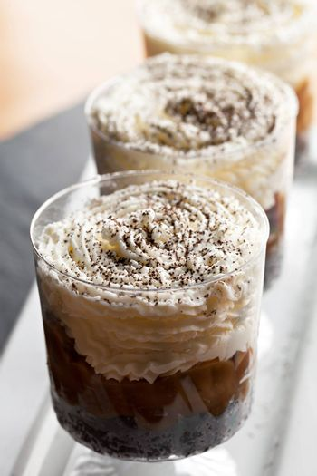 Banana caramel parfait desserts with fresh whipped cream and chocolate cookie crumbles. Shallow depth of field.
