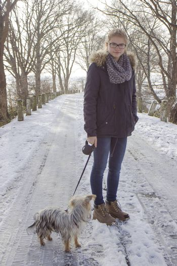young girl with her dog on the snow in winter