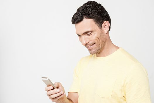 Smiling guy sending a text message