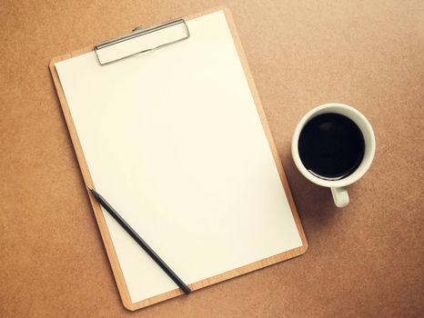 Blank white paper on clipboard with cup of coffee, retro filter effect