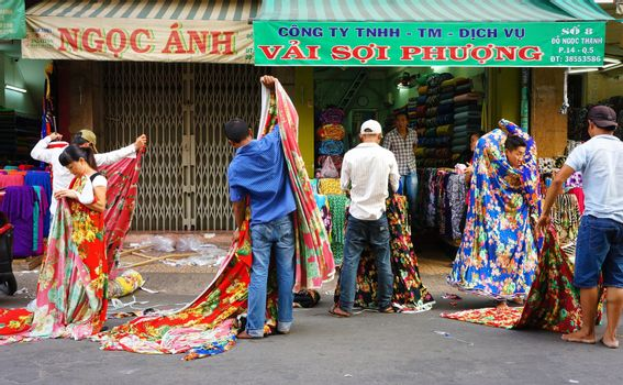 HO CHI MINH CITY, VIET NAM- DEC 28: Asia fabric market, colorful roll of cloth for clothing show at store, Vietnamese worker working at shop, garment industry develop to export, Vietnam, Dec28, 2014