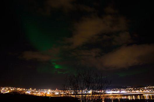 beautiful aurora borealis over the arctic city of tromsoe on a late autumn night