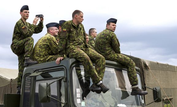 VILNIUS, LITHUANIA - MAY 17, 2014: Lithuanian army soldiers sitting on the top of military truck during Public and Military Day Festival in Vilnius, Lithuania