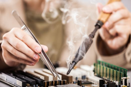 Human hand holding soldering iron repairing computer circuit boa
