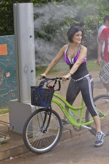 SAO PAULO, BRAZIL - FEBRUARY 01, 2015: An unidentified biker girl refresh at the water spray in the Ibirapuera Park at Sao Paulo Brazil.