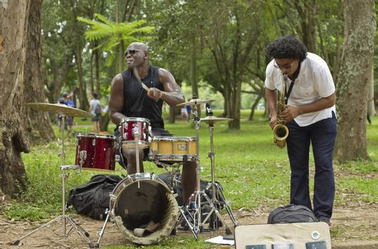 SAO PAULO, BRAZIL - FEBRUARY 01, 2015: An unidentified street musician singing and playing drums in the Ibirapuera Park at Sao Paulo Brazil.
