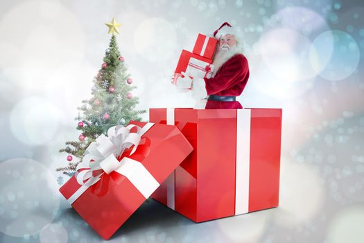 Santa standing in large gift against light glowing dots on blue