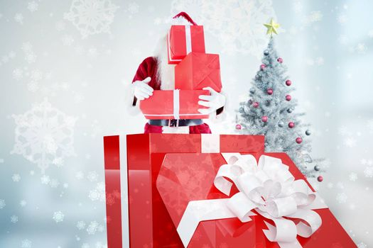 Santa standing in large gift against digitally generated delicate snowflake design