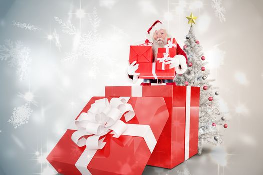 Santa standing in large gift against snowflake design shimmering on silver