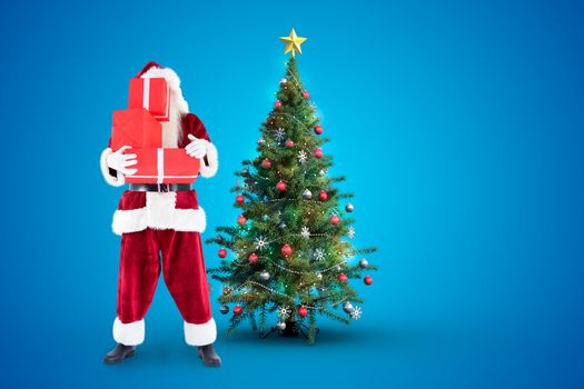 Santa covers his face with presents against christmas tree
