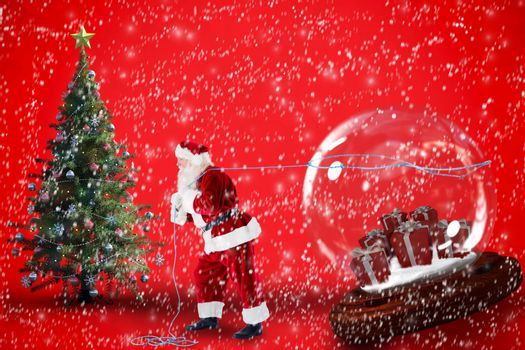 Santa pulling snow globe of presents against red background