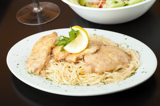 Chicken francaise or francese plated with pasta with salad in the background.
