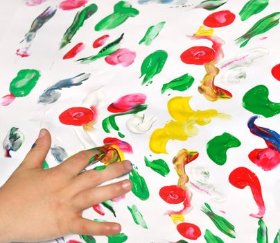 Painting with her fingers with different color paint