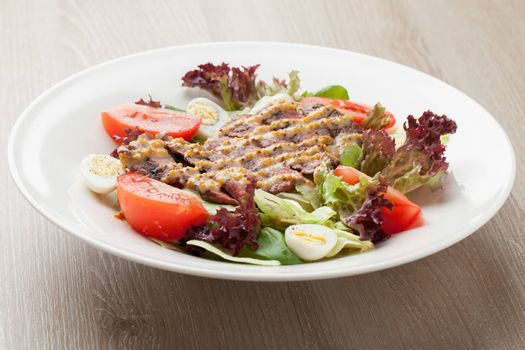 Fresh salad mix with grilled beef, meat cherry tomatoes , boiled quail eggs and  mustard  sauce served on table in white plate