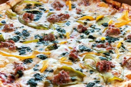 Close up detail of a fresh specialty pizza with spinach peppers and sausage.  Shallow depth of field.