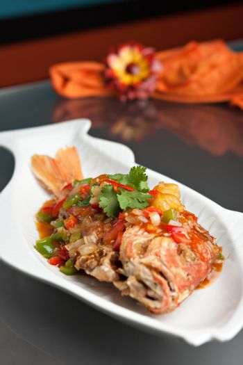 Freshly prepared Thai style whole fish red snapper dinner with tamarind sauce on a white fish shaped plate. Shallow depth of field.