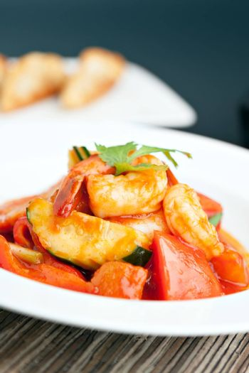 Thai style sweet and sour shrimp dish presented beautifully on a round white plate. Shallow depth of field.
