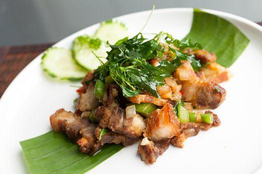 Traditional Thai crispy pork dish with green garnish.