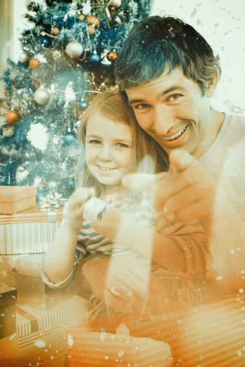 Father and little girl playing with Christmas presents against candle burning against festive background