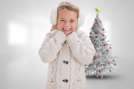 Cute girl in ear muffs against christmas tree in bright room