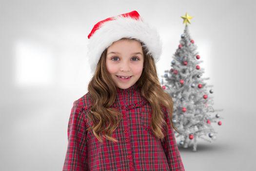 Cute girl in santa hat against christmas tree in bright room