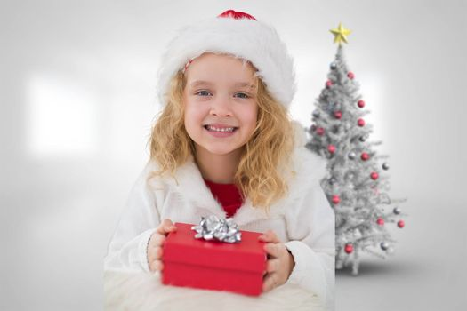 Cute girl with gift against christmas tree in bright room