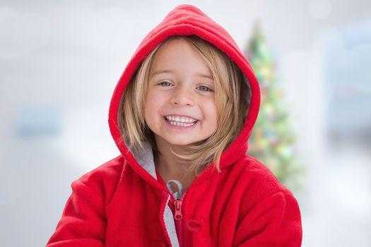 Cute girl in hooded jumper against blurry christmas tree in room