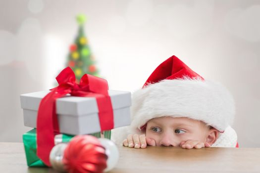 Cute boy looking at gifts against christmas tree in bright room