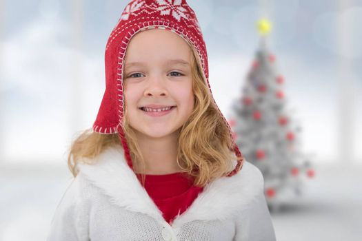 Cute girl in hat against blurry christmas tree in room