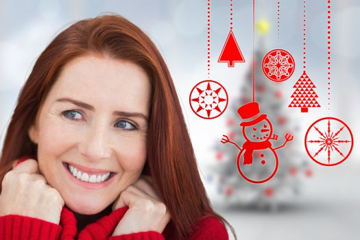 Happy redhead against blurry christmas tree in room