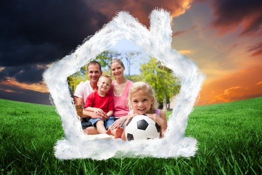 Composite image of little blond girl holding a soccer ball at a picnic