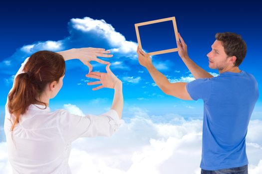 Composite image of couple deciding to hang picture