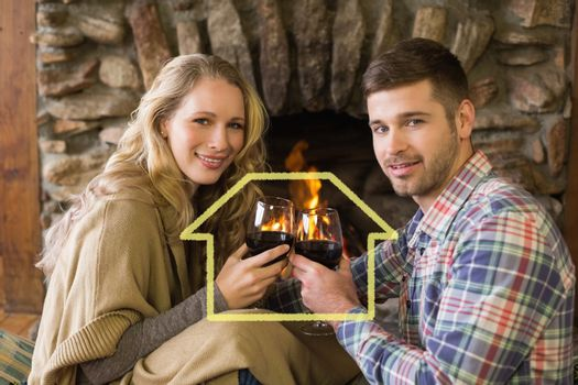 Romantic couple toasting wineglasses in front of lit fireplace against house outline