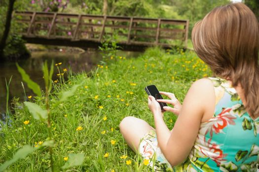 Woman text messaging in field