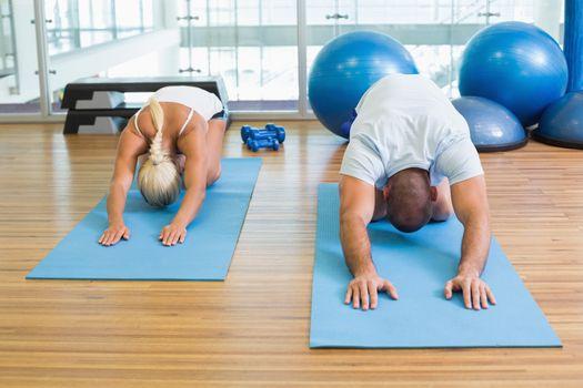 Couple in bending posture at fitness studio