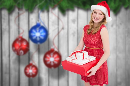Smiling woman with present against christmas baubles hanging over wood