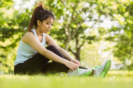 Healthy woman relaxing in park as she ties shoelace